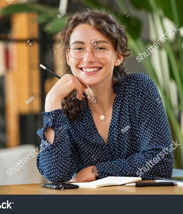 stock-photo-portrait-of-smiling-woman-wearing-spectacles-while-sitting-at-desk-business-woman-taking-notes-in-1886879992