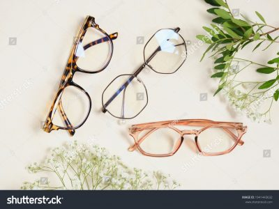 stock-photo-several-trendy-stylish-glasses-and-flowers-on-a-beige-background-place-copy-top-view-optics-shop-1941443632
